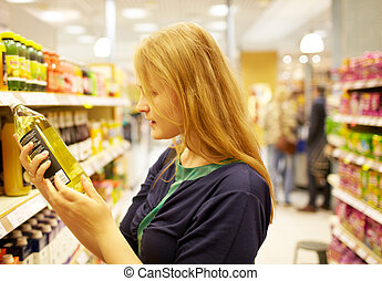 Young woman in the supermarket reading inscription - Young...