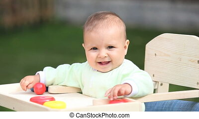 Baby - Adorable baby boy sitting on the childish chair...