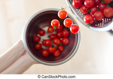 Cherry Tomatoes Tumbling From Metal Colander Into Metal Pan...