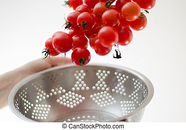 Cherry Tomatoes Tumbling Into Metal Colander - Ripe cherry...