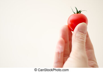 Cherry Tomatoe in Womans Fingers - A cherry tomato in a...