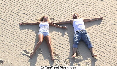 Resting - Happy couple resting on the sand together and...