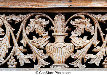 Old wooden carving with bowl and flowers on black background