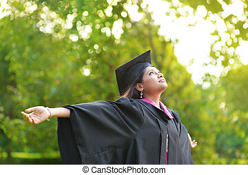 Graduation day - Young Asian Indian female student open arms...