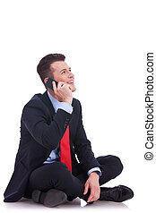 seated young business man talking on the phone and looking...