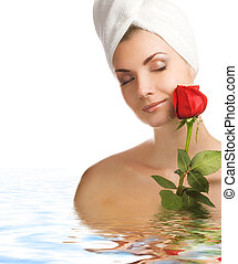 Beautiful young woman with a rose in water