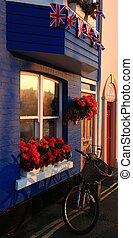 traditional seaside terraced house - British flags hung...