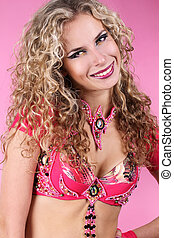 Happy smiling belly dancer girl with curly blond hair over ping background