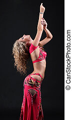 Beautiful exotic belly dancer woman posing on black background