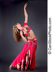 Beautiful exotic belly dancer woman posing on black...