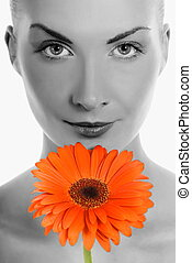 Beautiful young woman with gerbera flower