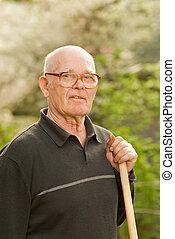 Elderly man relaxing after work in garden