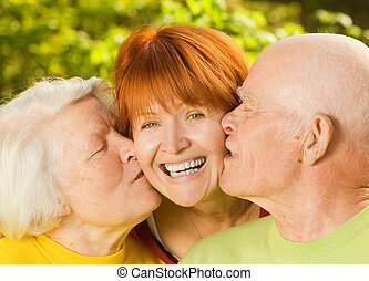 Senior parents kissing their daughter outdoors