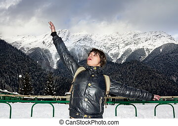 A girl stands, arms outstretched, amidst the mountain...