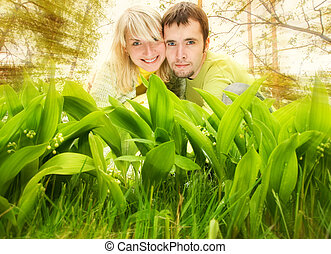 Young couple hiding in fresh green grass