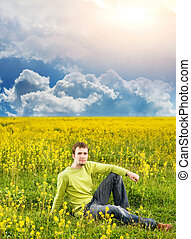 Relaxed young man sitting in a flower field