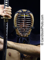 Closeup of kendo man - man holding samurai sword in dramatic...