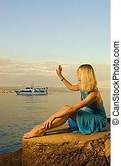 Beautiful young woman welcomes boat with tourists