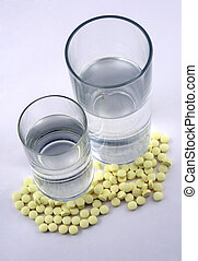 Tablets and a glass - Many yellow tablets and two glasses...
