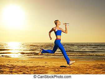 Beautiful young woman running on a beach at sunset (real shot, background is not photoshopped in)