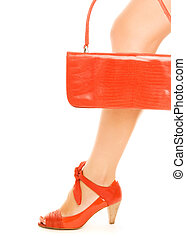 Kit of two classic items, sexy red shoe with high heel on a leg and elegant leather handbag