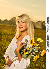 Young beautiful woman with a bouquet of sunflowers in thr...