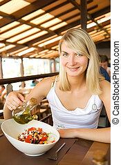 Beautiful young woman eating healthy vegetable salad in a...