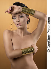 nude sexy girl with two big golden bracelets and hoope earrings, she is in front of the camera, looks in to the lens and has one arm on the chest and the left hand on the front