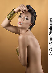 nude sexy girl with two big golden bracelets and hoope earrings, she is turned of three quarters at right, looks in to the lens and her right hand is near the front