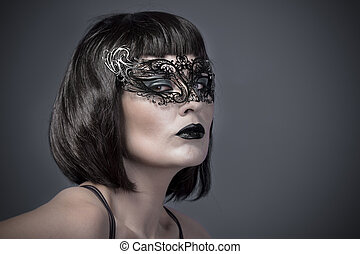 Beautiful woman with black mysterious venetian mask