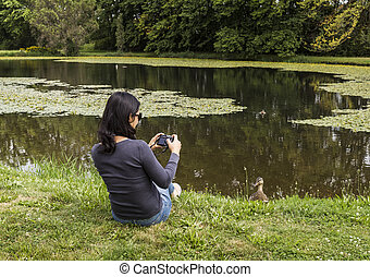 Bird Watching - Mature Asian women taking photos of Mallard...