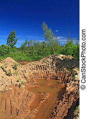 old sandy quarry in green wood