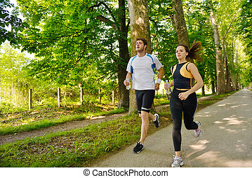 Young couple jogging in park at morning Health and fitness
