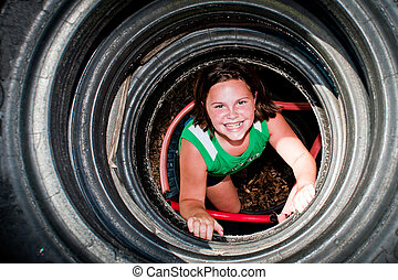 Girl plays in recycled tire tunnel at playground