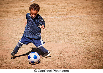 Young African American boy playing soccer
