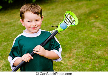Child playing lacrosse at park