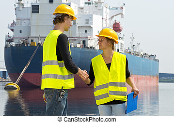 Technology deal - Female docker shakes hands with a male...
