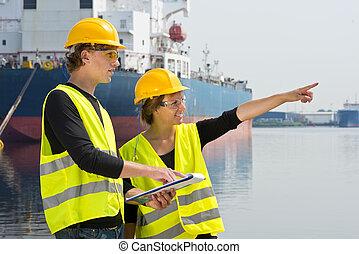 Industrial engineers - Two industrial engineers in a harbor,...
