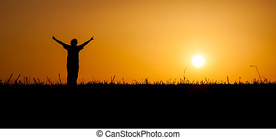 Person celebrating life at sunset - A person is celebrating...