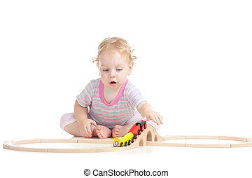 serious cute child is playing with wooden train isolated on white