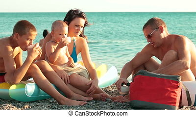 Family Summer Vacation On The Beach - Young family enjoying...