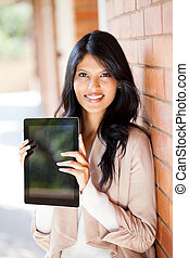beautiful young female university student holding a tablet...