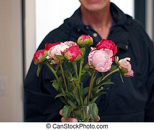 Man Giving Vase of Peonies