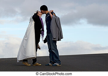 Wedding-day kiss - A groom carries his suit and a bride...
