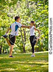 Couple doing stretching exercise after jogging - young...
