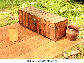 Vintage items - Wooden casket, clay pot and a mug on an old...