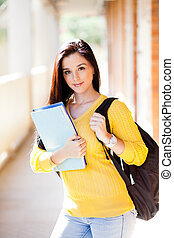 pretty female university student with books and backpack