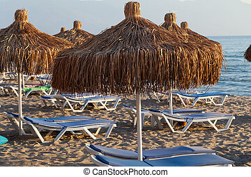 Beach loungers and umbrellas on the sea.