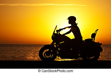 Woman biker over sunset, female riding motorcycle, motorbike...