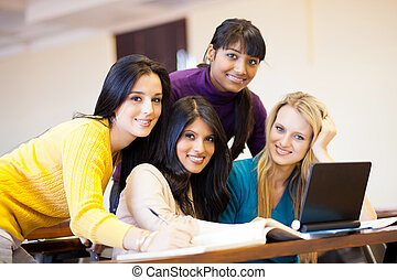 young female college students using laptop in classroom -...